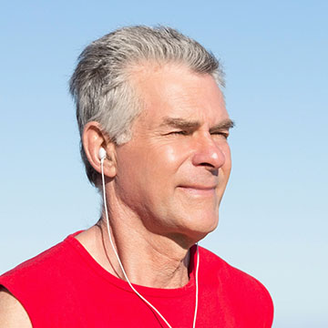 Senior man jogging with headphones listening to Beaumont HouseCall podcast