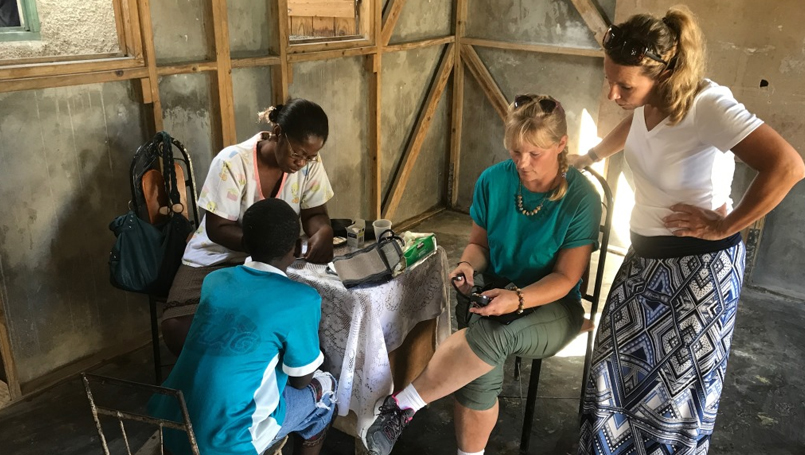 NA Kelli Paslawski checks a young Haitian patient's vital signs